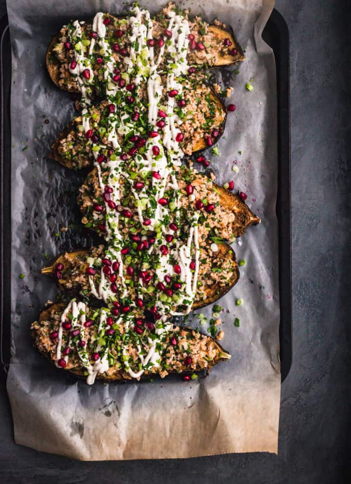 Bulgar Stuffed Eggplant with fresh herbs, tahini drizzle and pomegranate seeds all done and ready to be eaten.