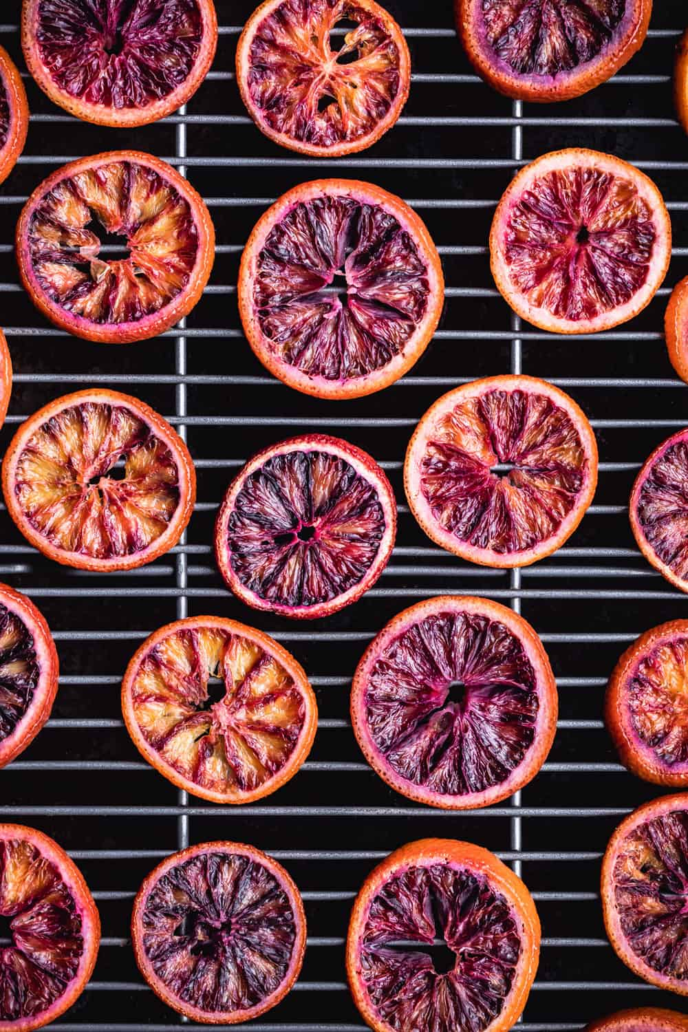 Blood Oranges have been candied and are drying on a cooling rack with a pan underneath to catch any excess drippings.