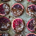 Candied Blood Oranges dipped in Chocolate with Flaky Sea Salt on a pan.