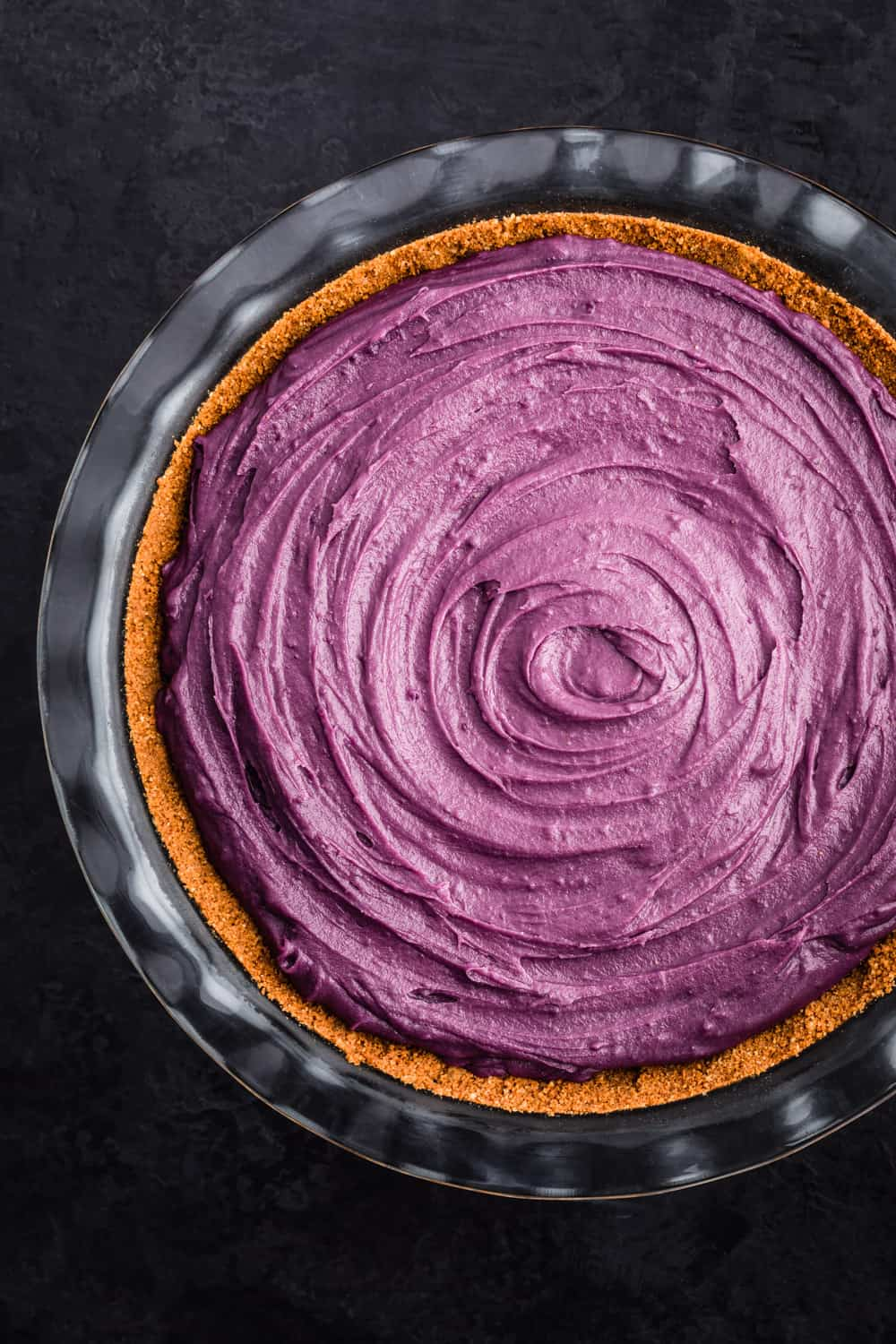 Purple sweet potato pie has been poured into the gingersnap curst and is ready for the oven.