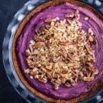 Purple sweet potato pie has been topped with pecan streusel.