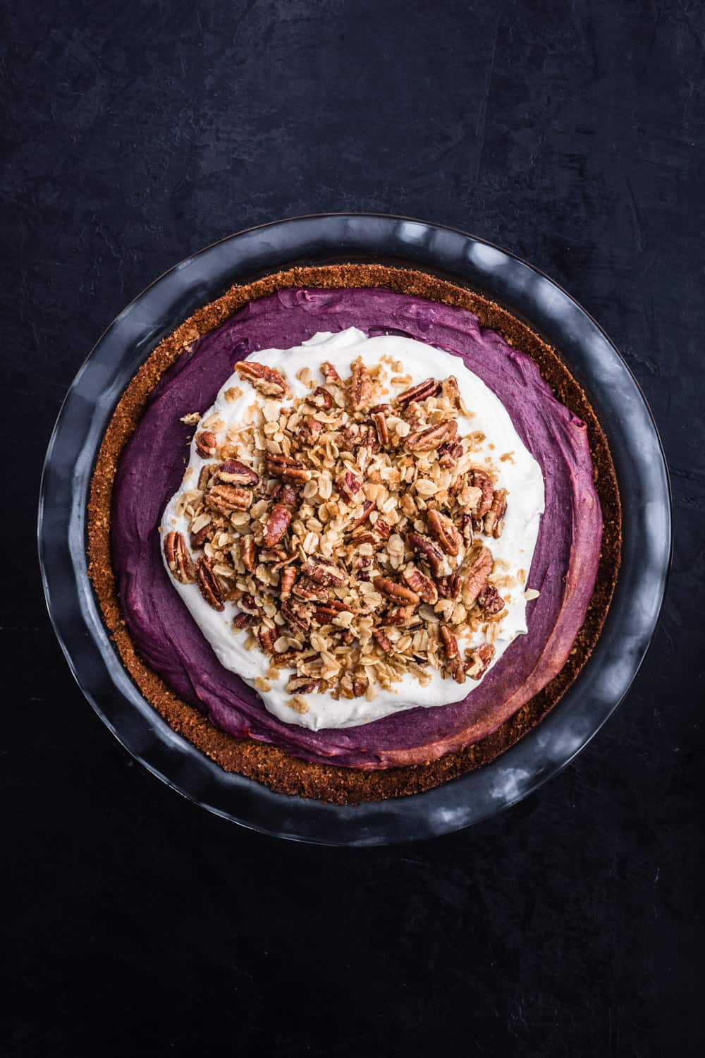 Purple sweet potato pie has been topped with whipped cream and pecan streusel on top.