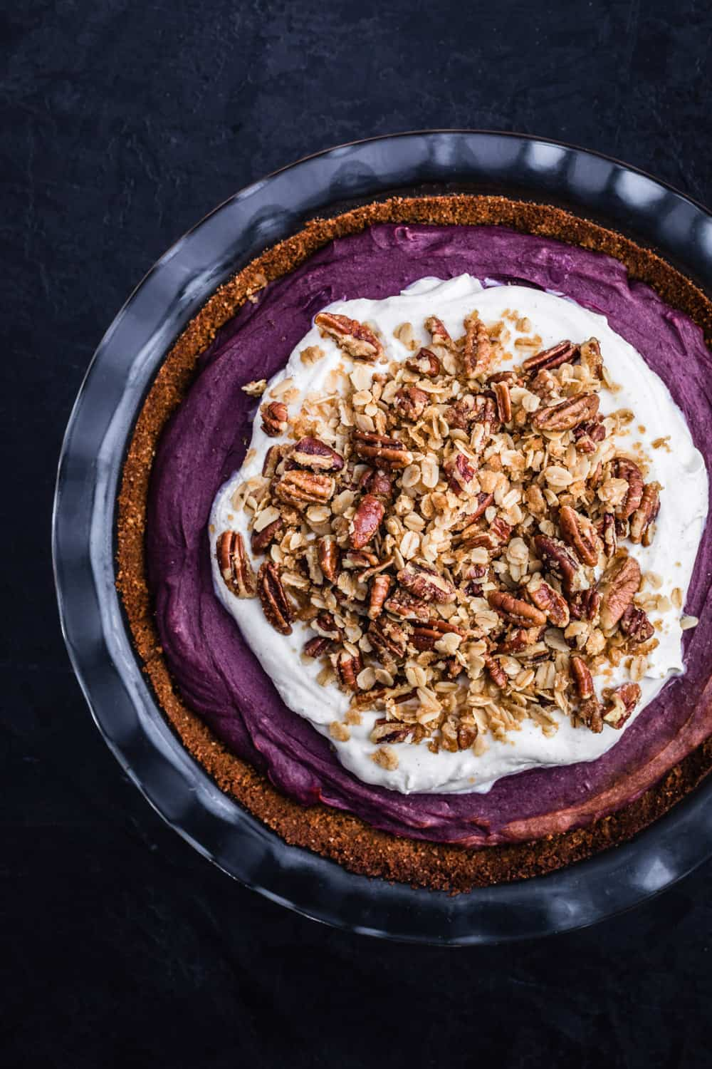 Up close of purple sweet potato pie has been topped with whipped cream and pecan streusel on top.