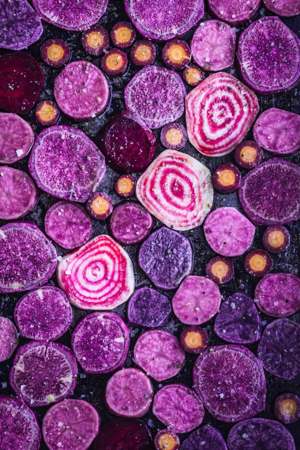 All sorts of purple root vegetables with salt, pepper and olive oil ready to go into the oven on a sheet tray.