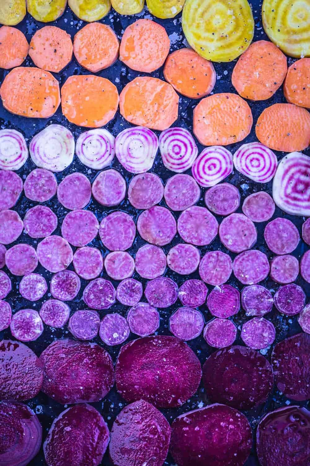 Rainbow Root vegetables on a sheet tray with olive oil, salt and pepper all ready for the oven.