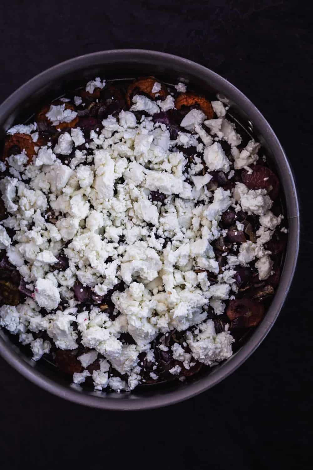 Tart pan with glaze, root vegetables, and goat cheese. In process shot of the tart being assembled.