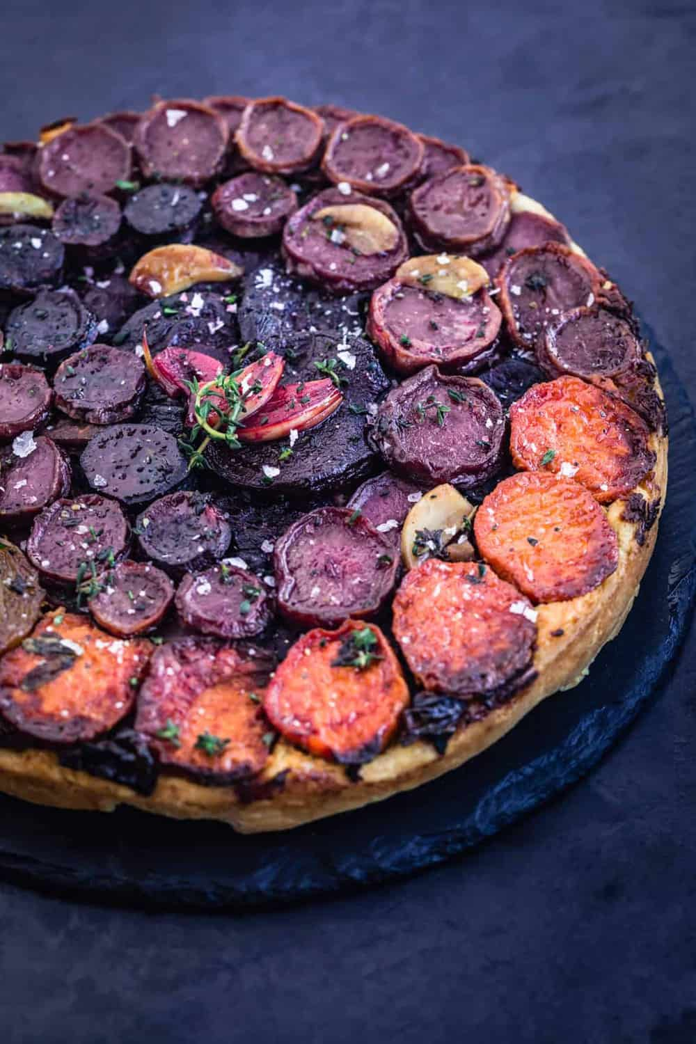 Rustic Rainbow Root Vegetable Tarte Tatin with fresh herbs and garlic all done. Side angle shot.