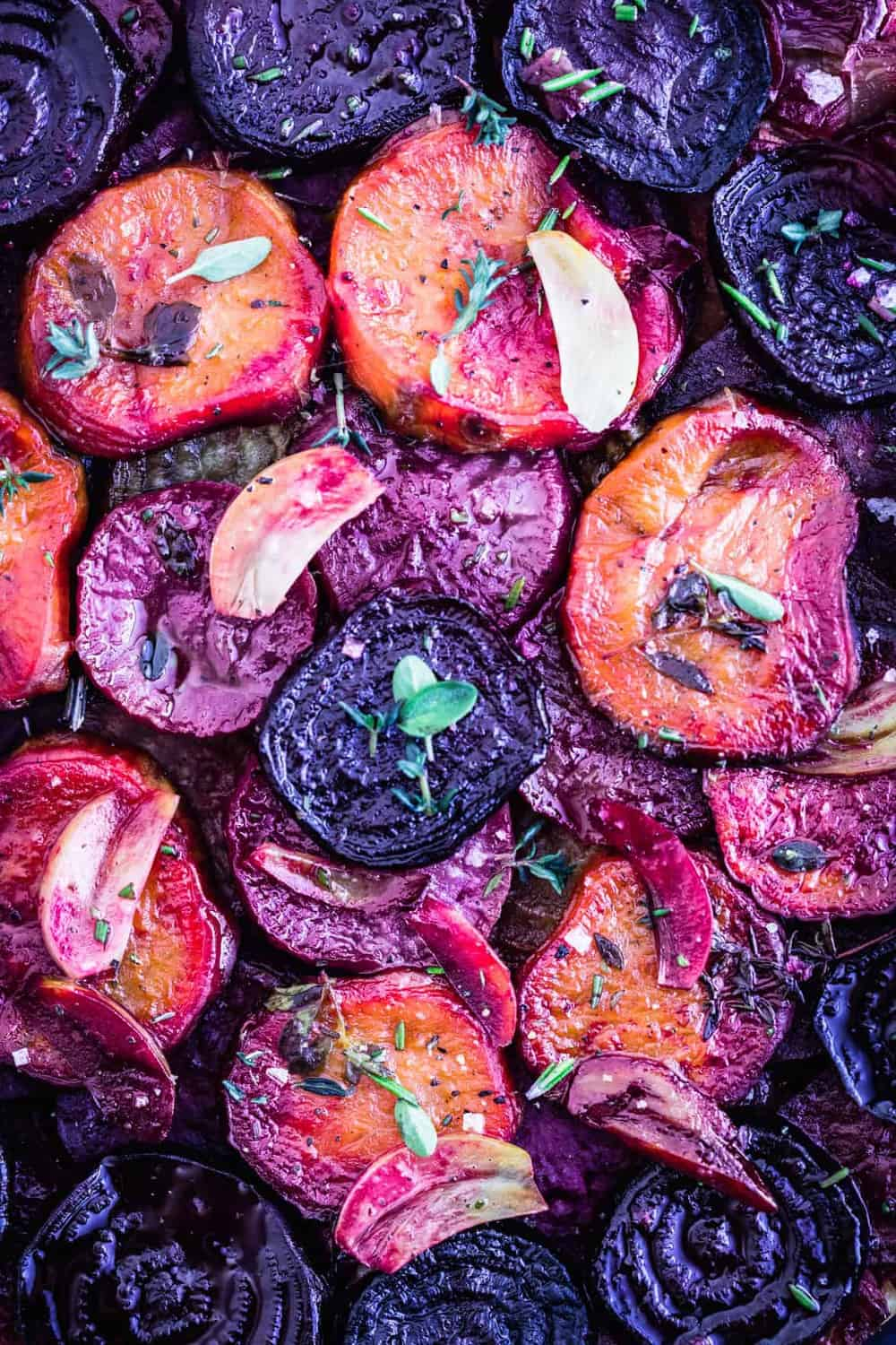 Root Vegetable Tarte Tatin with fresh herbs and garlic, very close up shot of the veggies.
