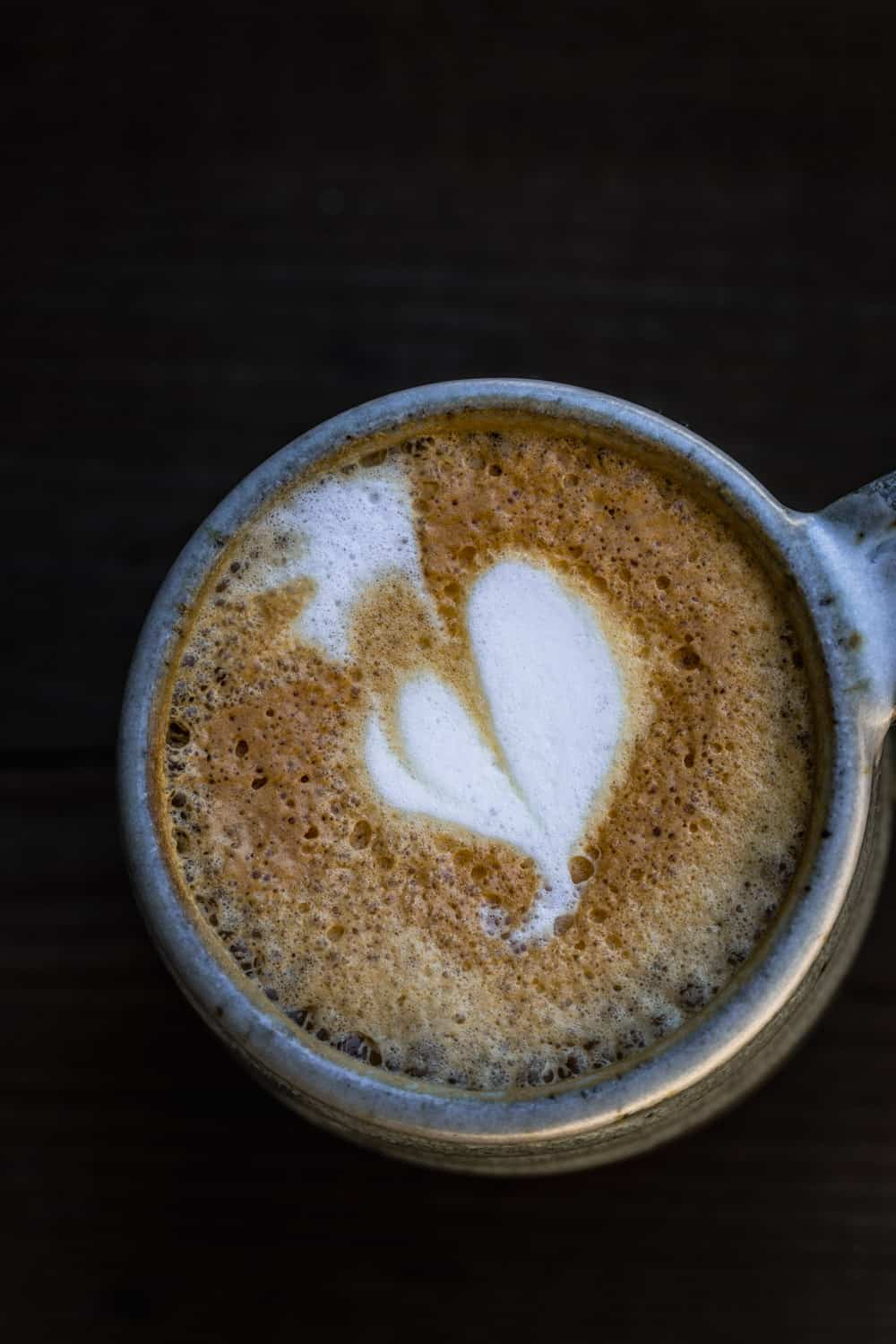 A cappuccino with a foam shaped heart in a ceramic cup.
