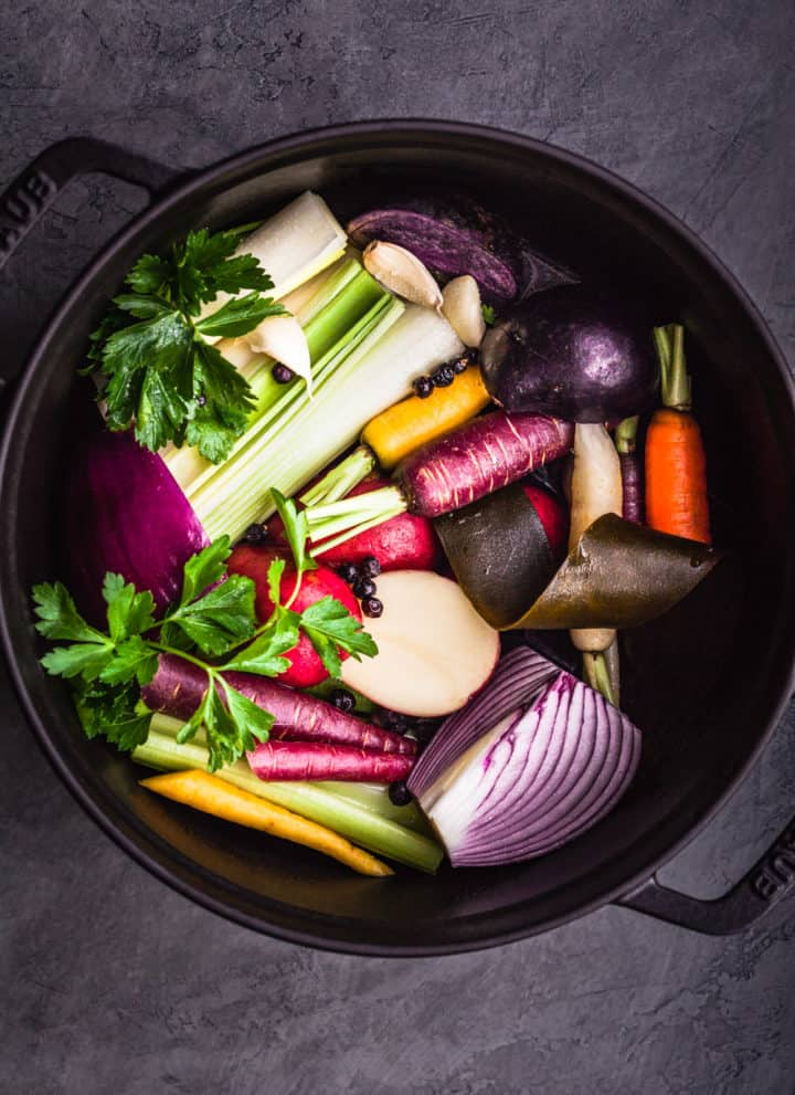 Overhead shot of Magic Mineral Broth in the making. A stock pot filled with leeks, celery, red onions, kombu seaweed, carrots, garlic, parsley and peppercorns.