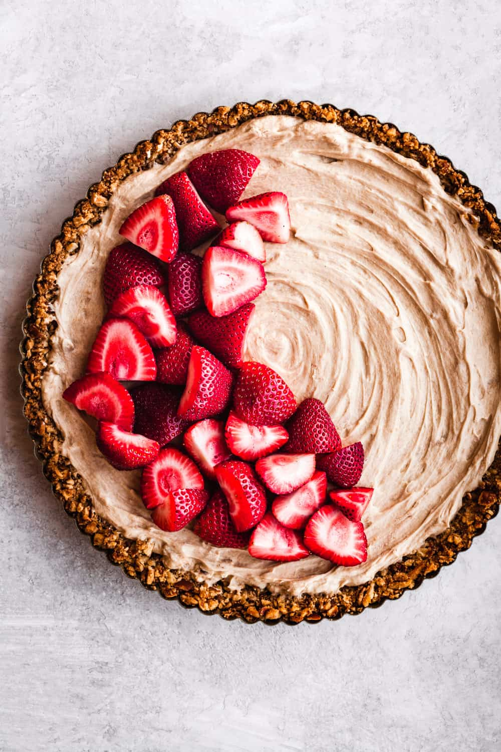 No-Bake Strawberry Cheesecake with a pretzel crust, overhead shot on a white background.