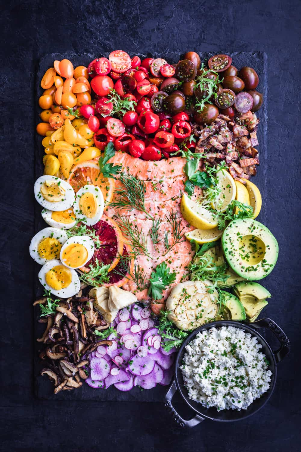 Salmon Rainbow Party Salad Board with eggs, tomatoes, bacon, avocado, mushroom, feta, radishes, oranges and garlic.