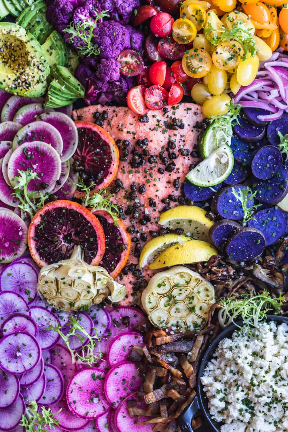 Salmon Rainbow Party Salad Board with avocado, purple cauliflower, tomatoes, red onions, purple patties, pink and purple radishes, bacon, cheese, garlic, blood orange and watermelon radishes. Up close.