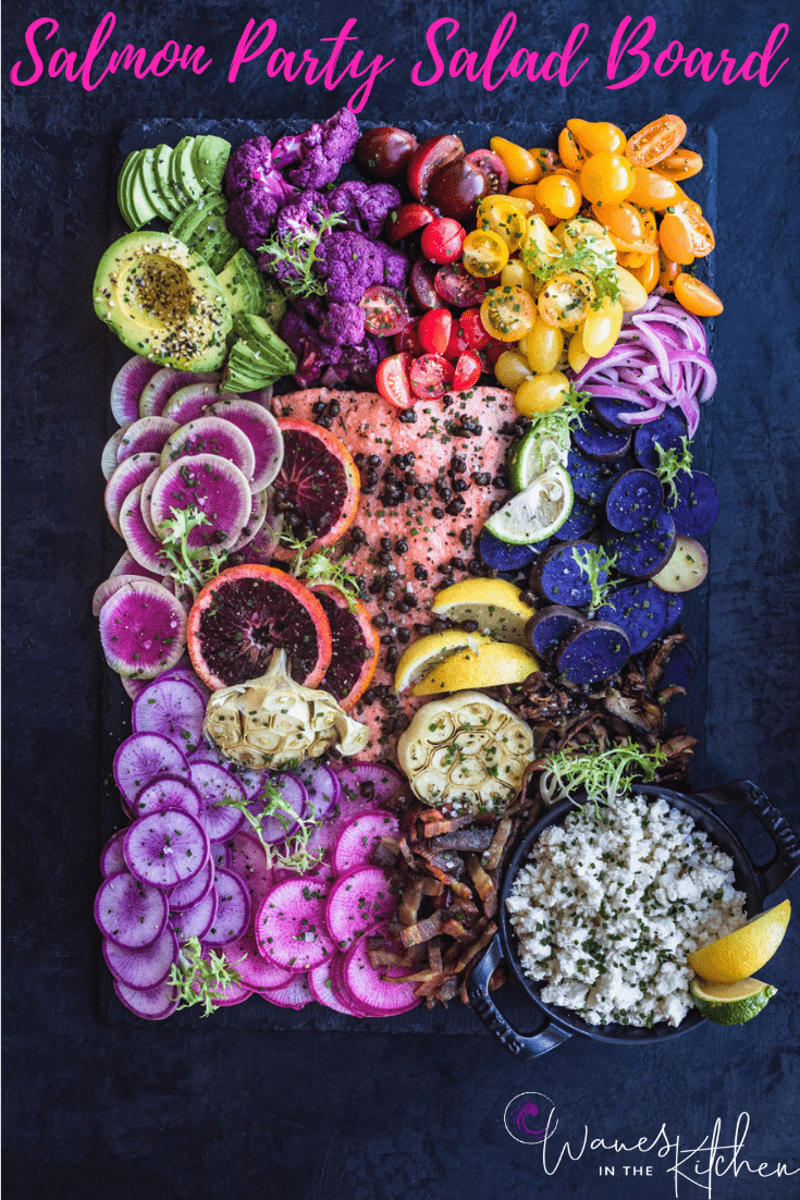 Salmon Rainbow Party Salad Board with avocado, purple cauliflower, tomatoes, red onions, purple patties, pink and purple radishes, bacon, cheese, garlic, blood orange, lemons, limes and watermelon radishes. Up close. Overhead shot,
