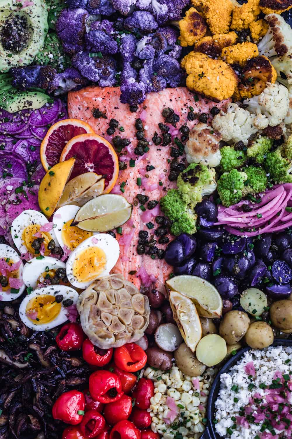 Salmon Rainbow Party Salad Board with avocado, purple, white, green and yellow cauliflower, pickled red onions, purple and white potatoes, corn, cheese, peppers, garlic, mushrooms, soft boiled eggs, ninja and watermelon radishes, blog oranges, lemons, limes, fried capers and shallots. Up close shot.