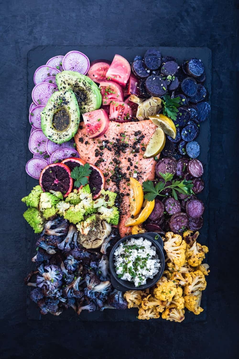Salmon Rainbow Party Salad Board with ninja radishes, avocado, tomatoes, purple and pink potatoes, garlic, yellow and purple cauliflower, romanesco, blood oranges, garlic, lemons, limes and cheese sprinkled with fresh herbs and fried capers.