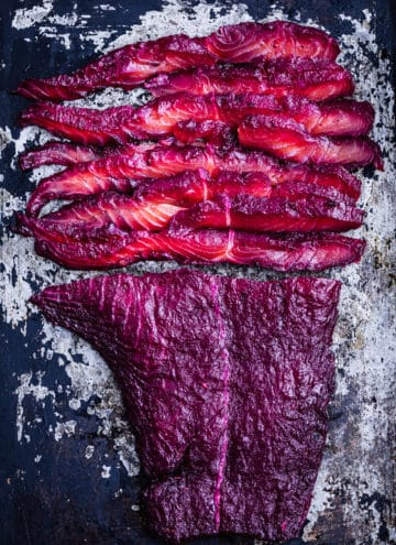 Thinly sliced beet cured salmon on a cookie sheet.
