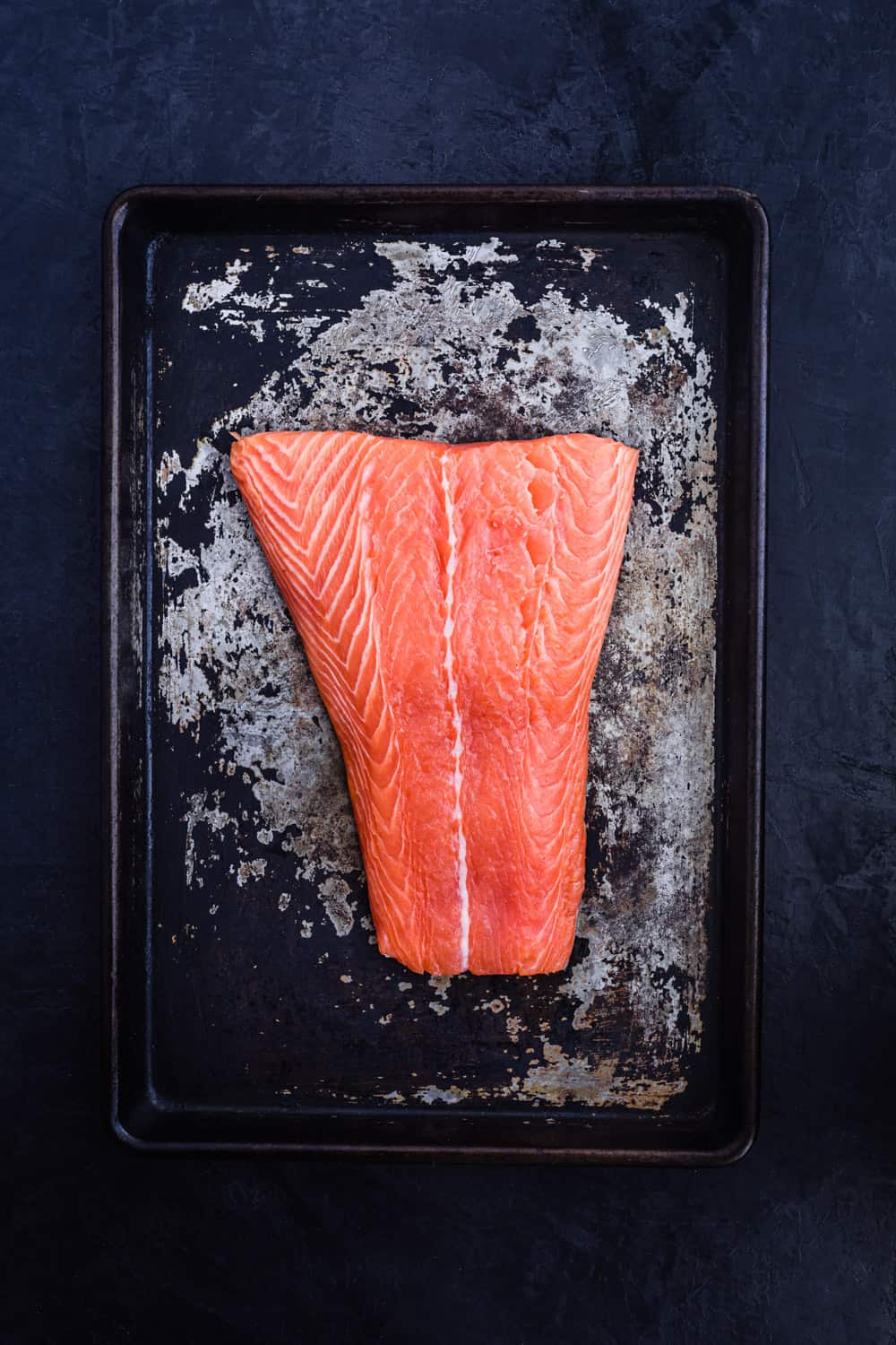 In process shot of the salmon fillet on a cookie sheet, ready for the next steps.