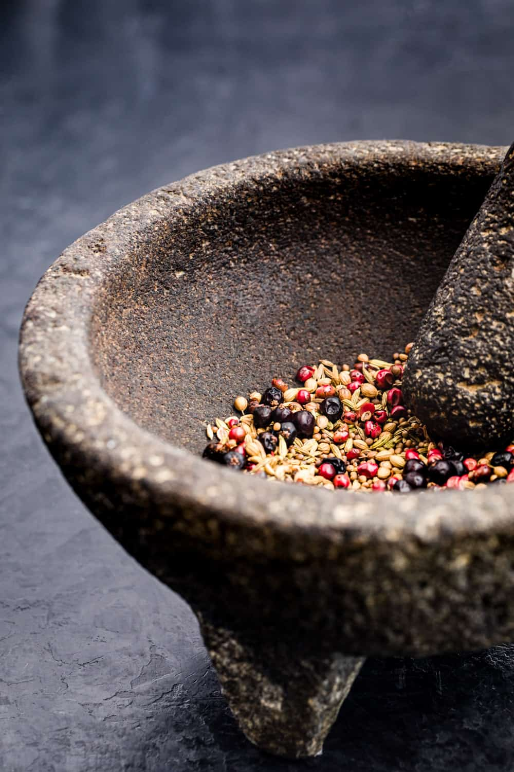 Whole spices, pink peppercorns mustard seeds, fennel seeds, juniper berries and coriander in a mortar and pestle ready to be ground up.