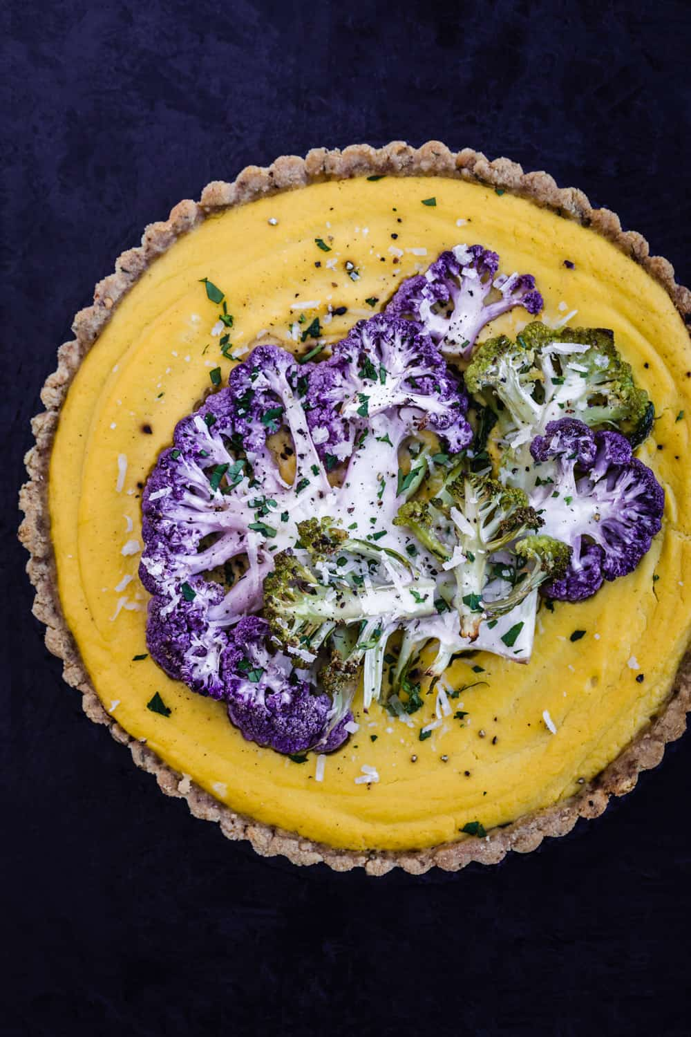 Yellow cauliflower tart, topped with purple and green thinly sliced cauliflower, post-oven.