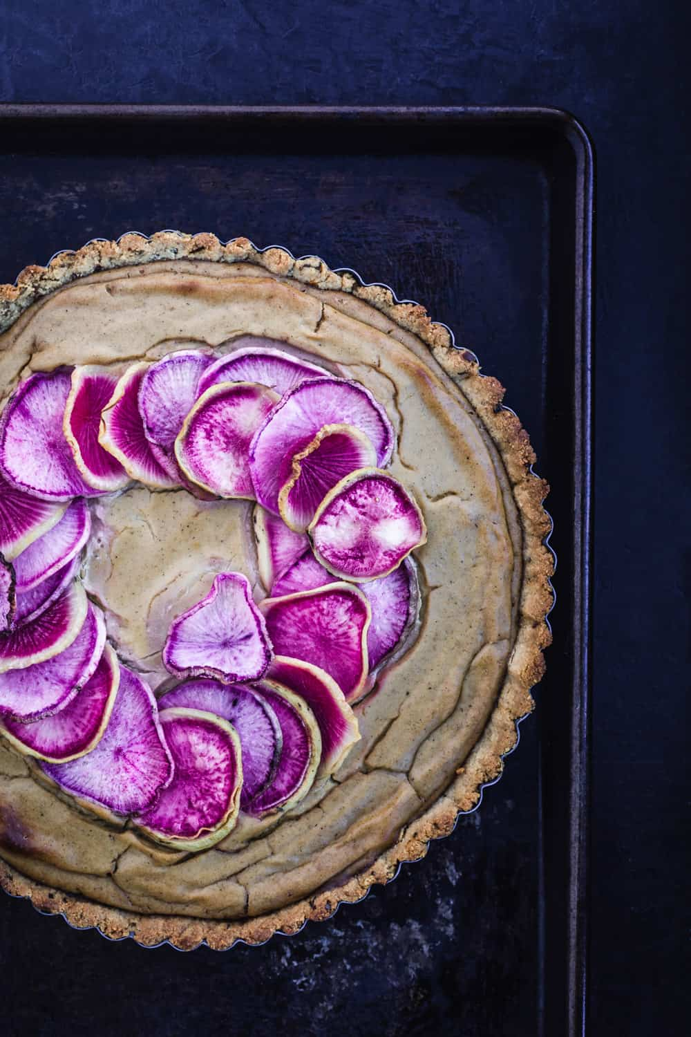 White cauliflower Tart with a Garlic & Herb Almond Crust topped with pink and purple radishes all done!