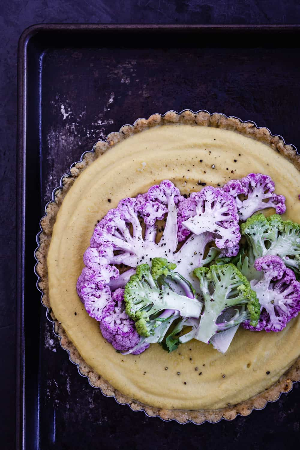 Yellow cauliflower tart, topped with purple and green thinly sliced cauliflower, pre-oven.