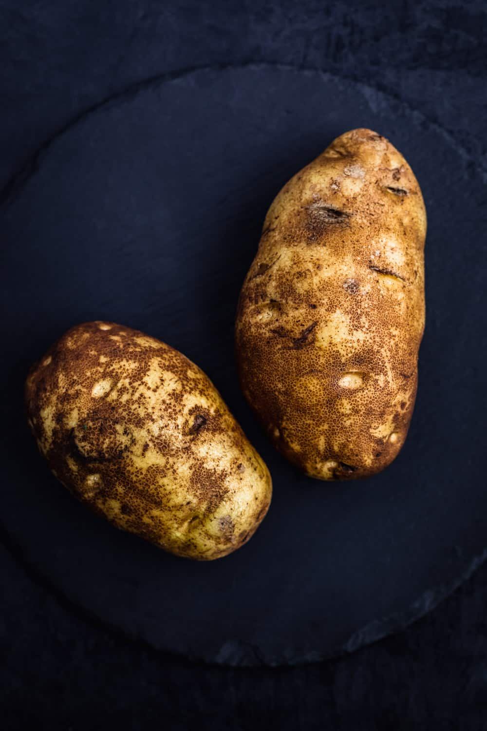 2 russet potatoes, screened and unpeeled on darrk background.