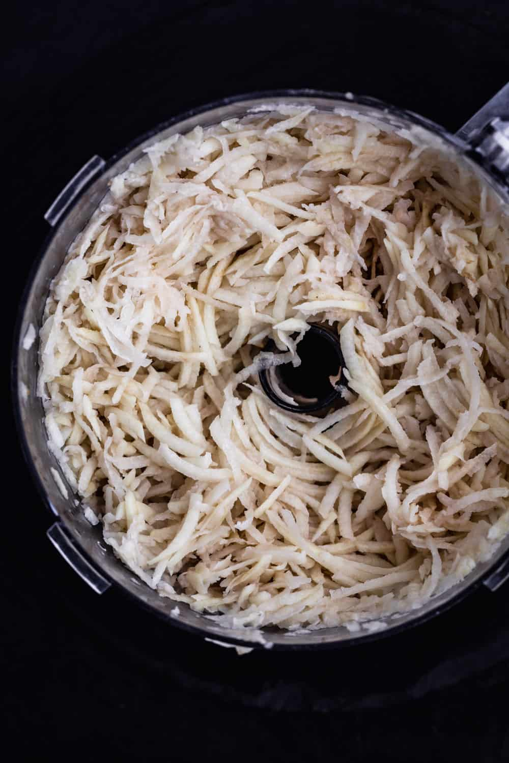 Inside of food processor shot with the shredded potatoes.