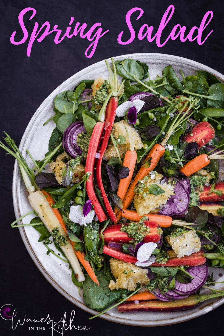 Spring salad with carrot top pesto, snap peas, garlic croutons, edible flours, ninja radishes, watercress and mint on a white plate.