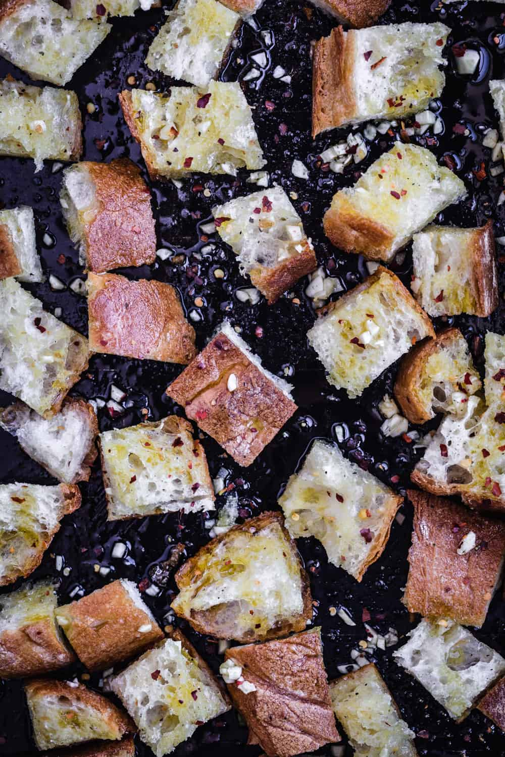 Croutons in the making! Bread is tossed with olive oil, garlic, chili flakes, salt, pepper and ready for the oven.