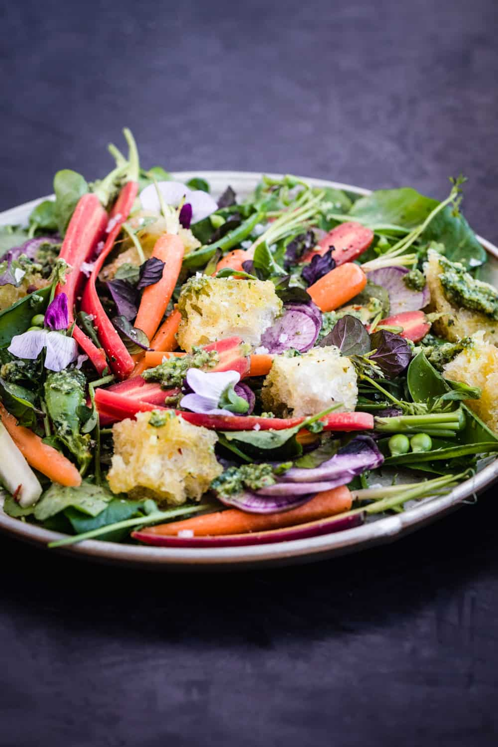 Side angle shot of the spring salad with carrot top pesto, snap peas and garlic croutons. with edible flours, ninja radishes, watercress and mint.