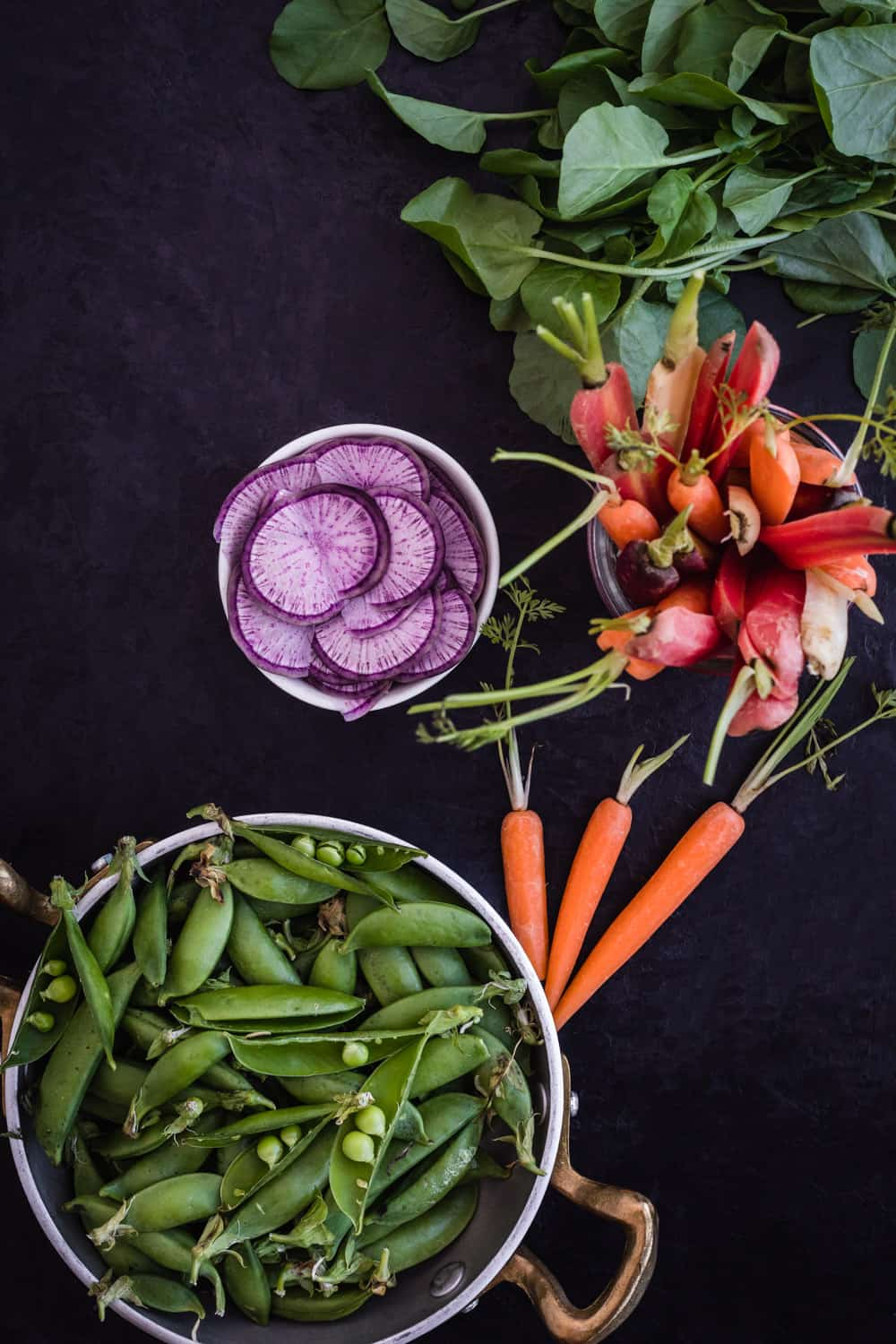 Ingredient shot of snap peas, radishes, carrots and watercress.