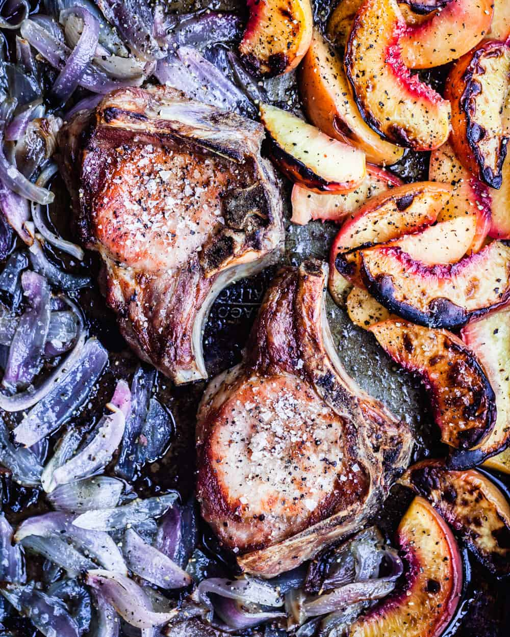 Peachy bone-in pork chops, all done with charred red onions, overhead shot.