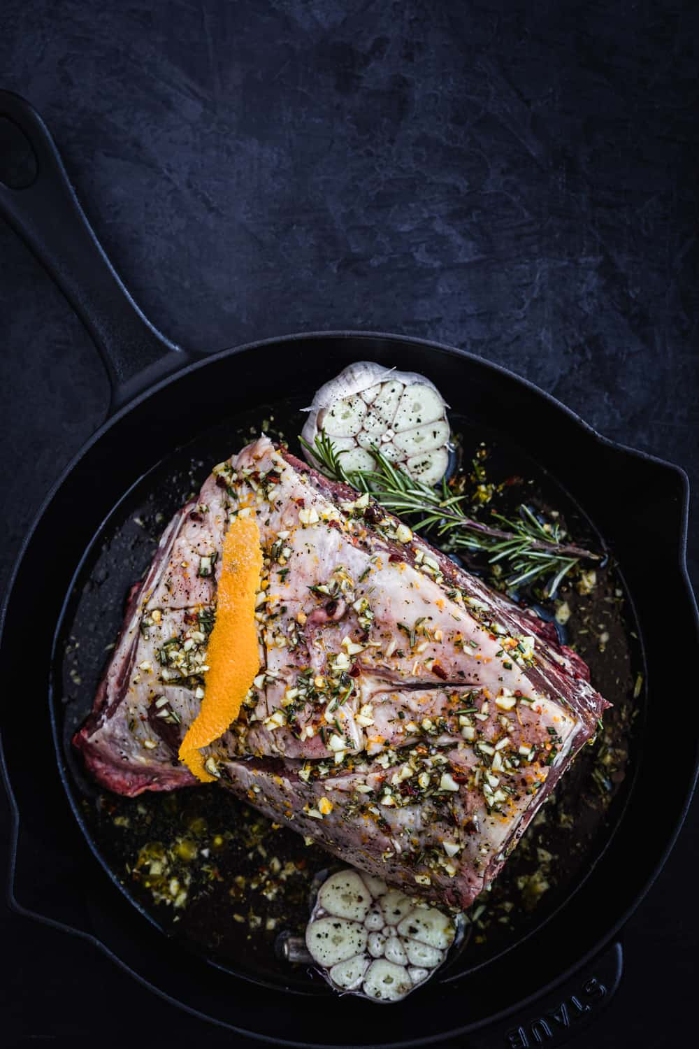 Lamb shoulder with rosemary, garlic and orange zest, in a cast iron skillet all ready for the oven.
