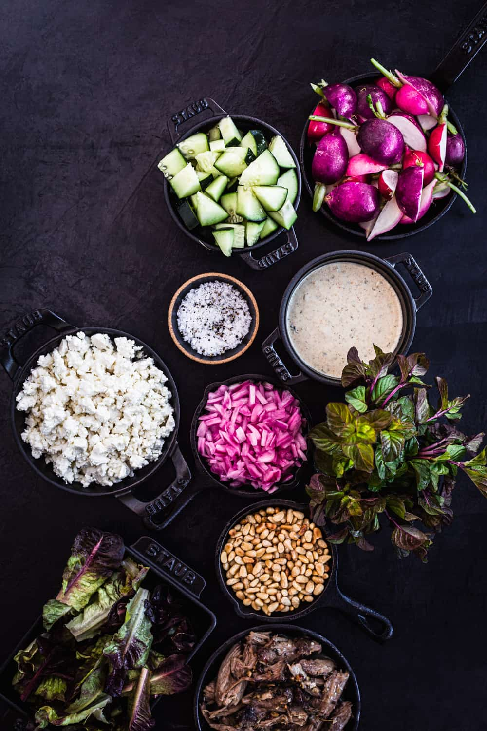 Ingredient shot with cucumbers, feta, radishes, little gems, lamb, pine nuts, pickled red onions, yogurt, salt and pepper.