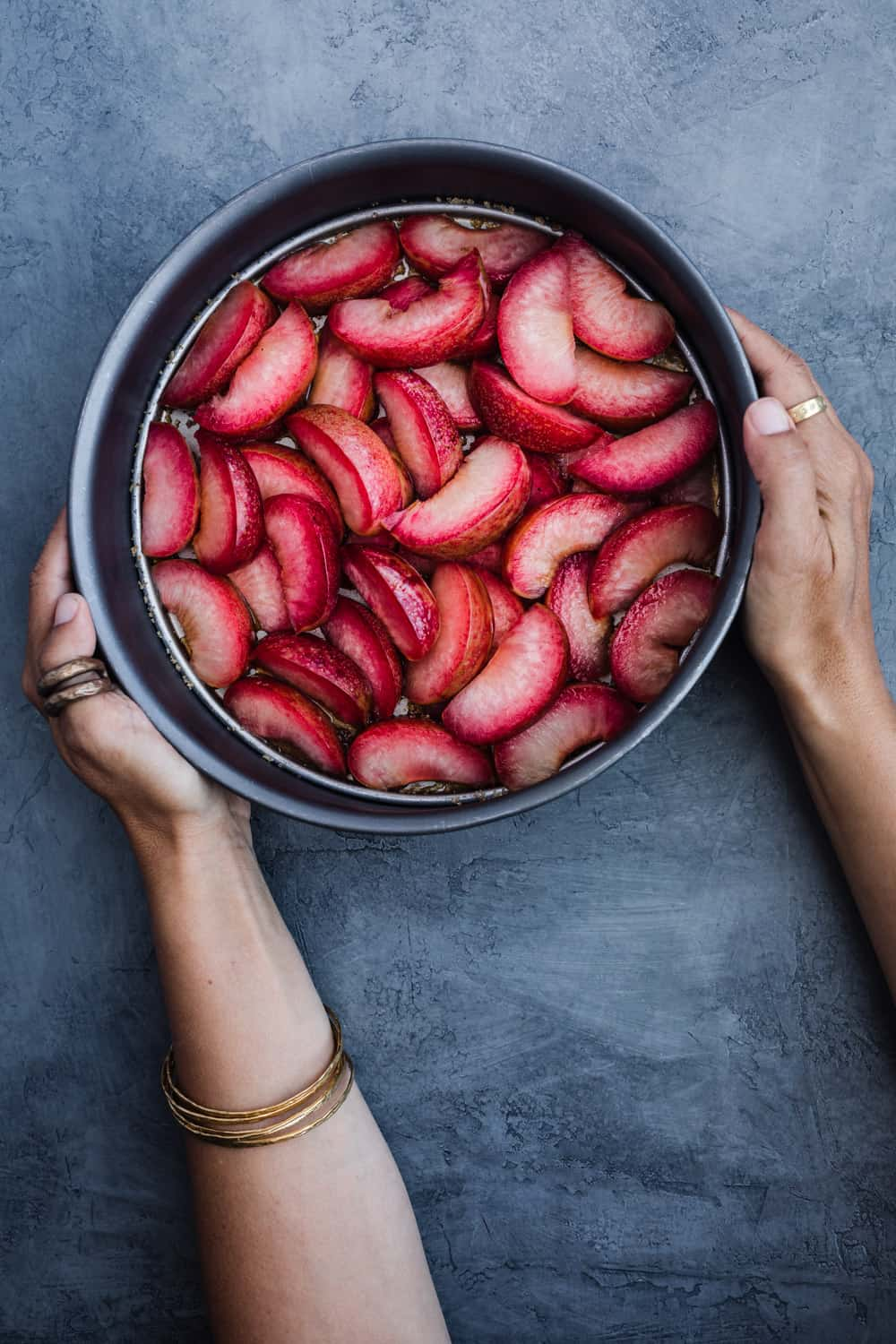 Chef Daniela Gerson holding the cake pan with the plum slices arranged in it.