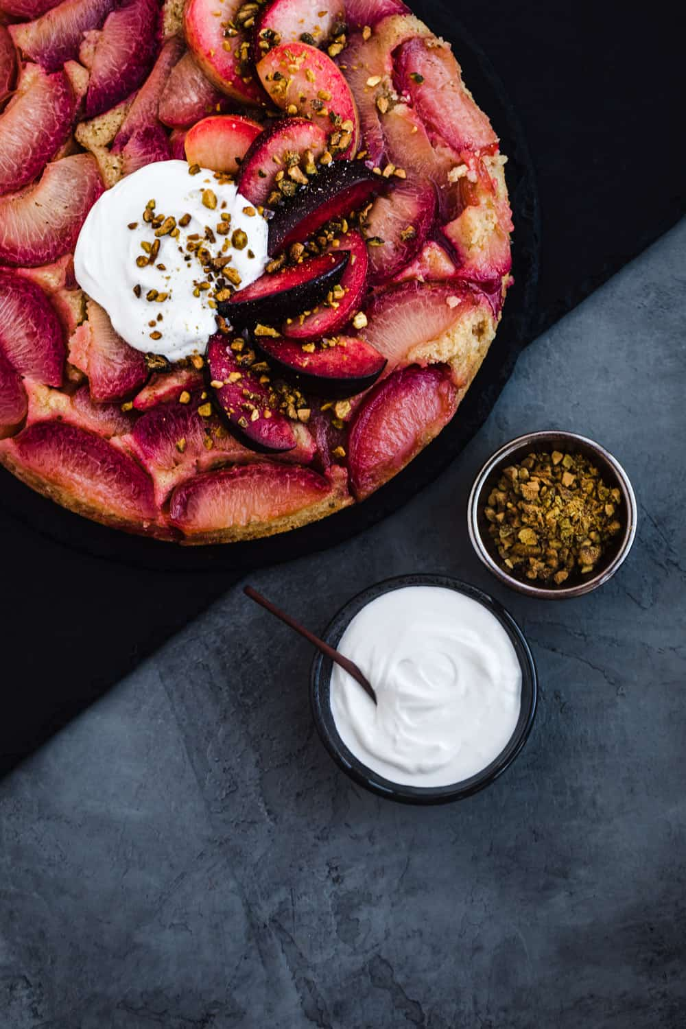 A stylized food shot of the plum upside down cake, a bowl of yogurt and a bowl of pistachios.