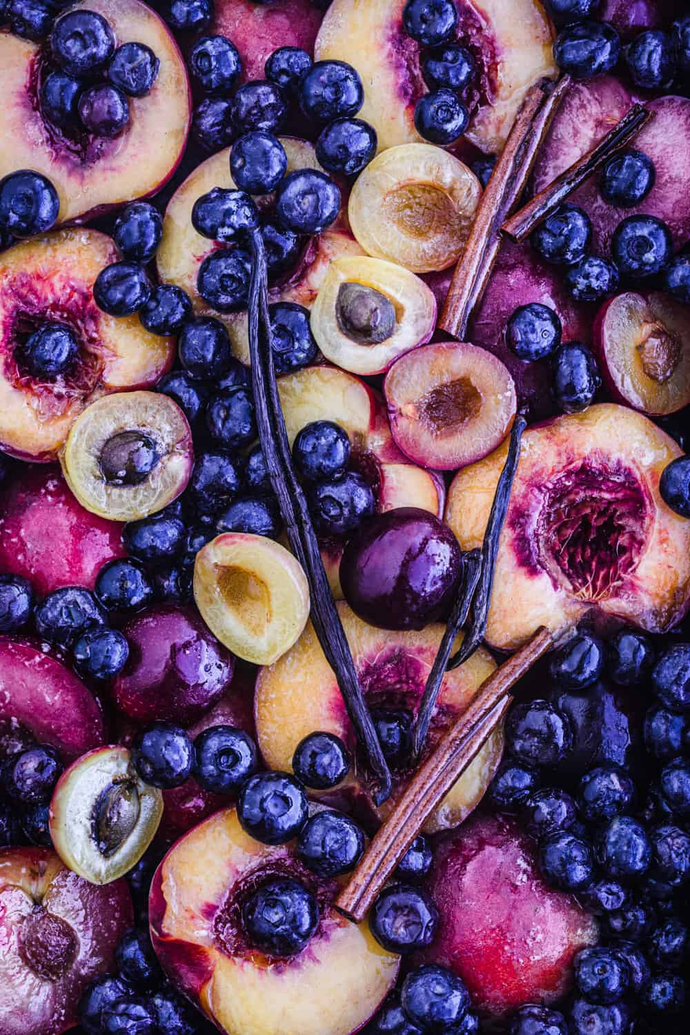 In process shot with peaches, stone fruit, blueberries, drizzled with butter, with vanilla and cinnamon.