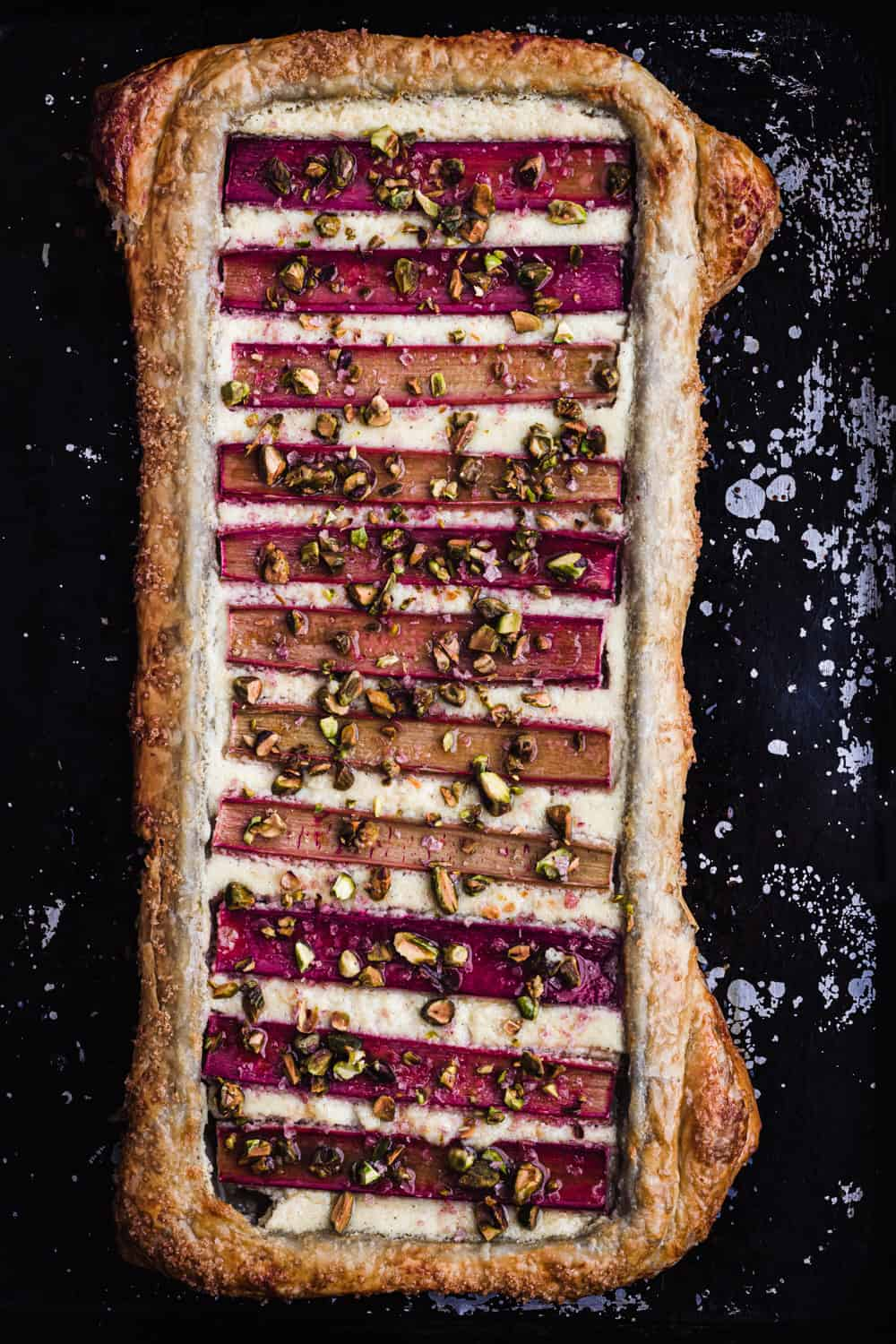 Overhead shot of the finished rhubarb tart drizzled with honey and crunchy pistachios, overhead shot.