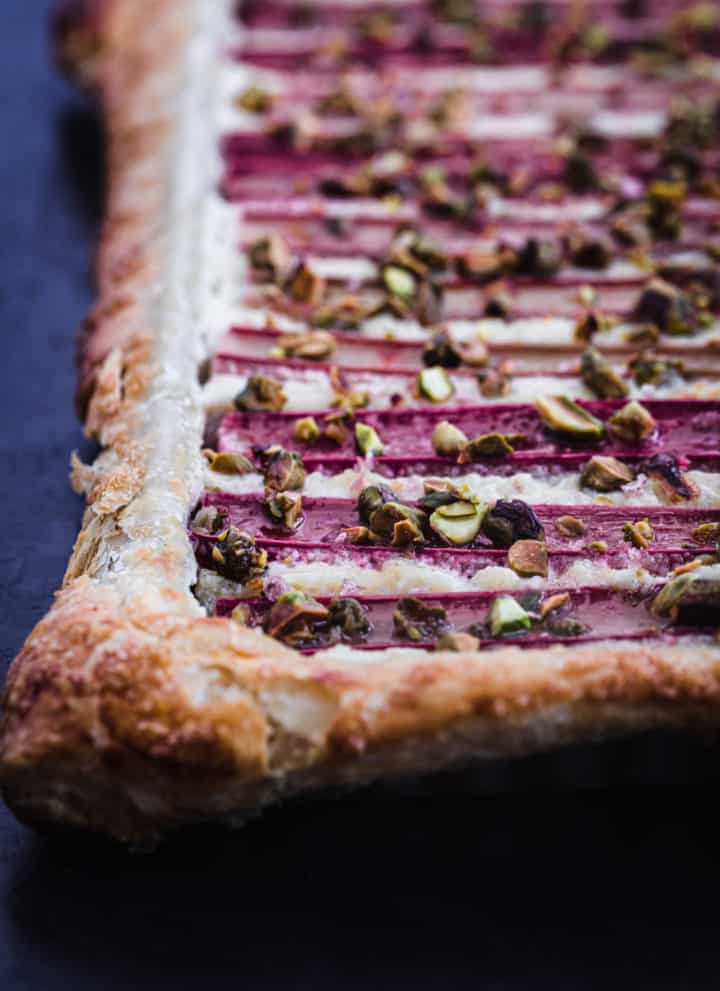 Up close side angle shot of the finished rhubarb puff pastry tart. Can see the honey drizzle and pistachios on top.