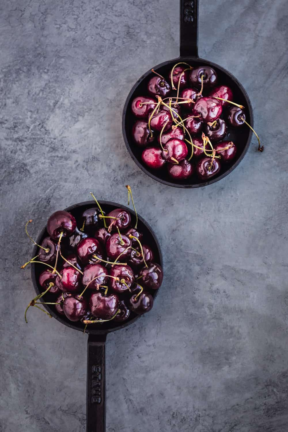 2 skillets filled with whole, raw cherries, overhead shot.