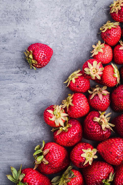 Ingredient shot of unstemmed strawberries, arranged on a grey background.