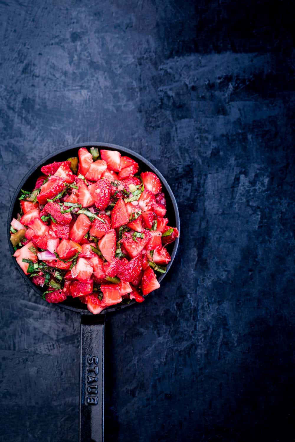 the finished strawberry salsa in a mini serving skillet on a black background.