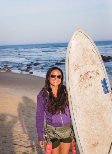 Chef Daniela Gerson holding her surfboard in Ditch Plains, NY.