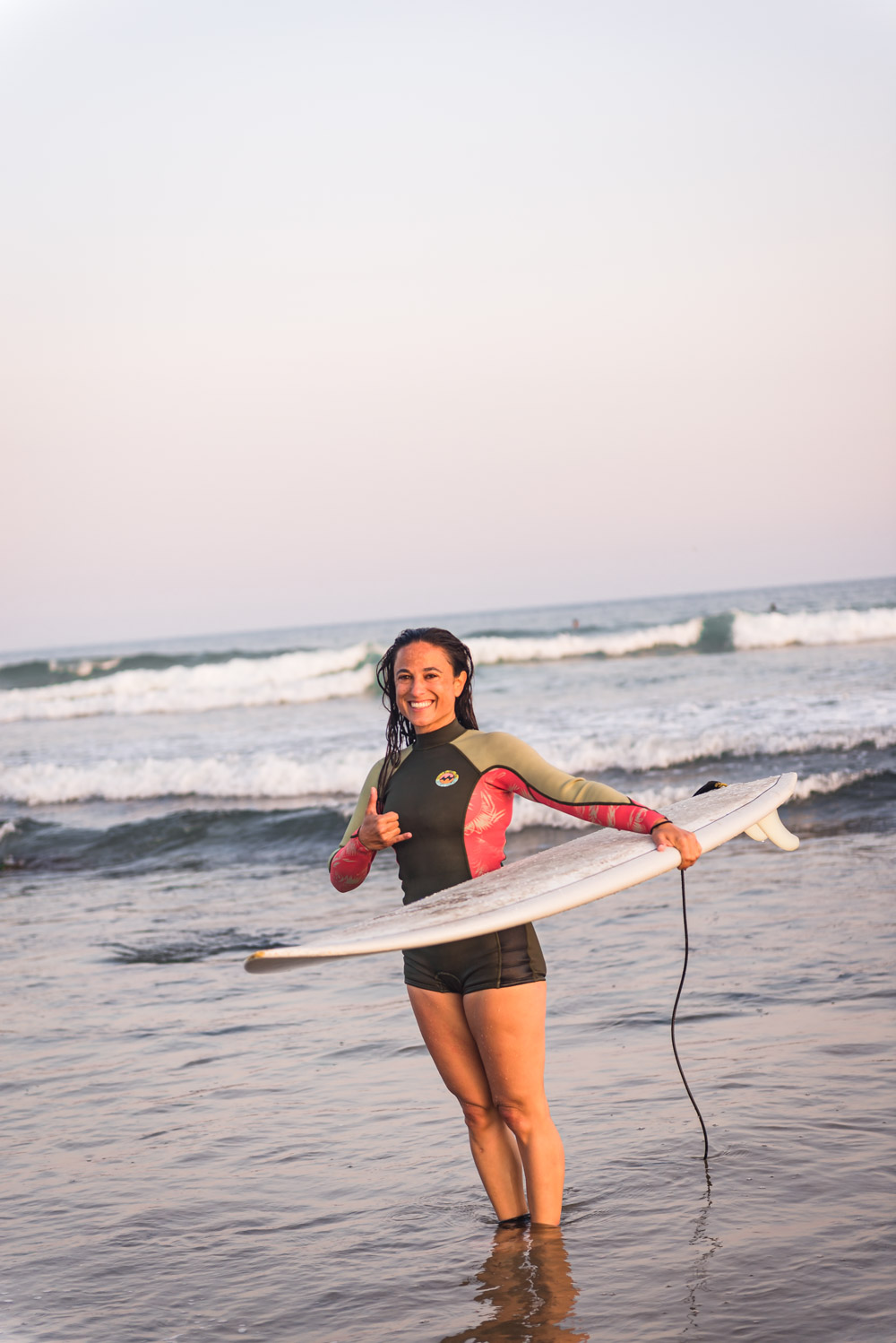 Chef Daniela Gerson, post surf session, in her wetsuit giving a shaka to the camera.