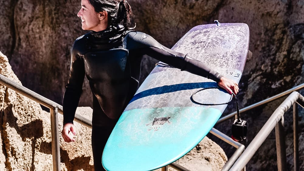 Chef Daniela Gerson carrying her board out of the water after surfing in Santa Cruz.