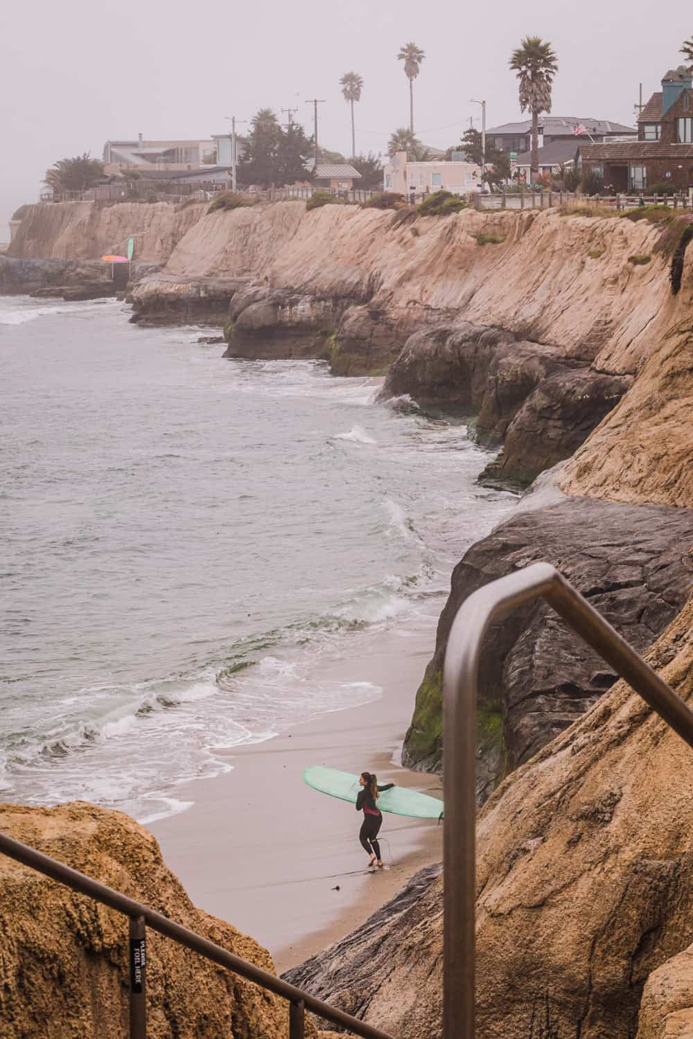 A view of Pleasure Point, where the cliffs meat the ocean, and a surfer about to paddle out