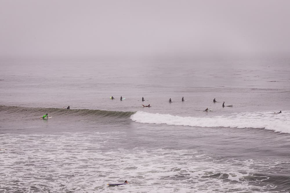 surfers in the line up in Santa Cruz on foggy day