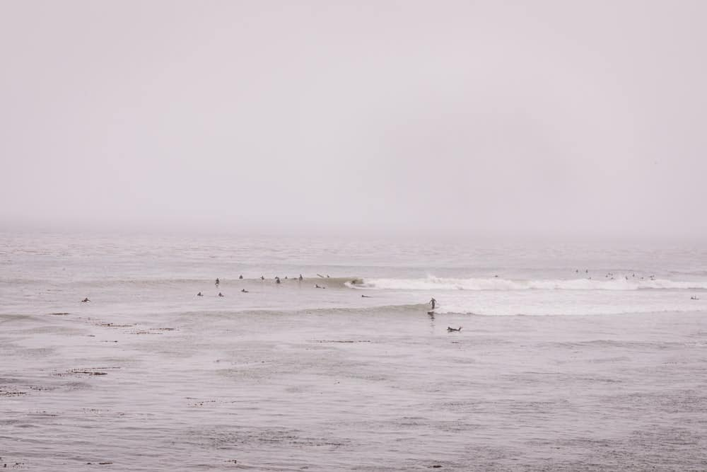 a view of surfers in the ocean in Santa Cruz on a foggy day