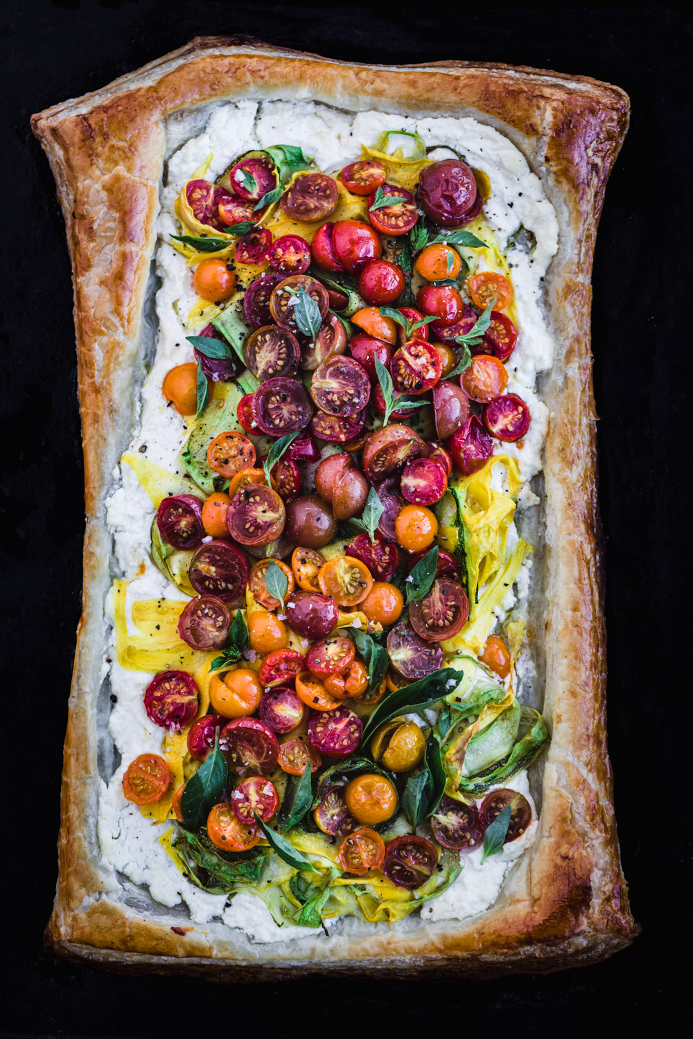 Rainbow tomato puff pastry tart with summer squash ribbons and basil, freshly out of the oven.